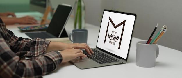 Seitenansicht der weiblichen büroangestellten, die auf modell-laptop-tastatur auf arbeitstisch im büroraum tippt Premium PSD