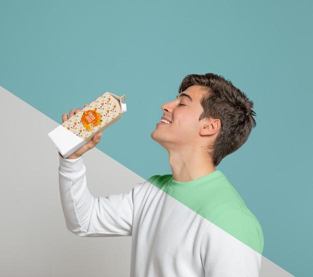 Seitenansicht des mannes, der aus saftkarton trinkt Kostenlosen PSD