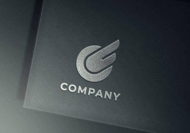 Silber geprägtes logo-modell auf grau strukturiertem papier Premium PSD