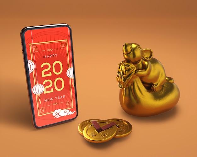 Smartphone neben goldener statue für neues jahr Kostenlosen PSD