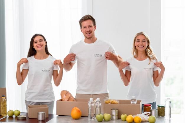 Smiley-freiwillige halten ihre t-shirts in der hand, während sie essen für die spende vorbereiten Kostenlosen PSD