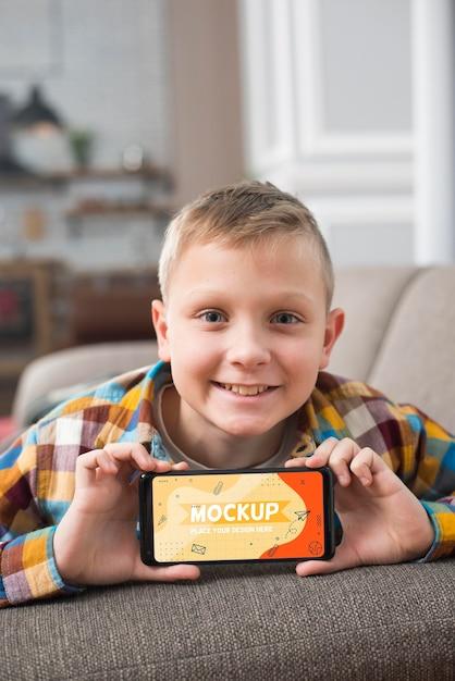 Smiley-kind auf der couch, die smartphone hält Kostenlosen PSD