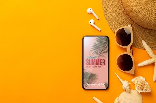 Sommerhintergrund mit telefonmodellschablone und strandzubehör auf lebendigem orange hintergrund Premium PSD