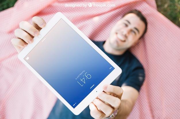 Tablet-modell mit dem mann, der auf stoff liegt Kostenlosen PSD