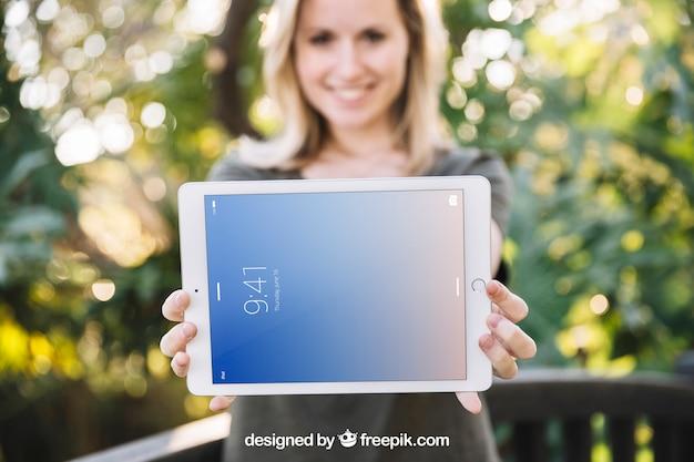 Tablet-modell mit frau in der natur Kostenlosen PSD