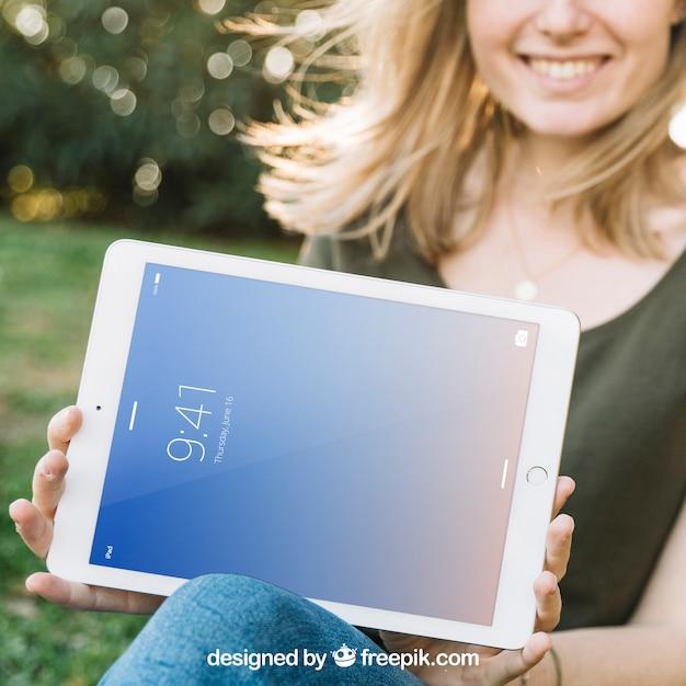 Tablet-modell mit lächelnder frau draußen Kostenlosen PSD