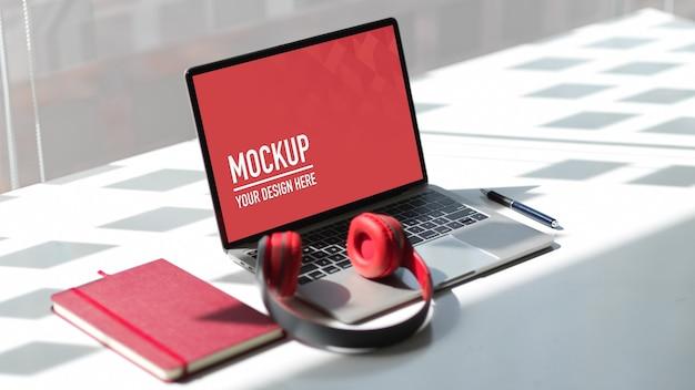 Tragbares laptop-modell im arbeitsbereich mit kopfhörer Premium PSD