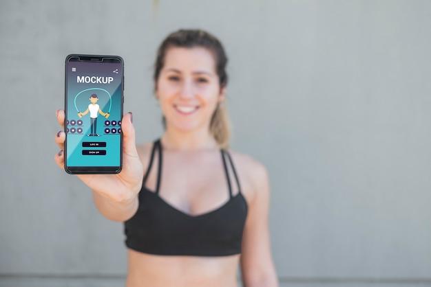 Verschwommene frau in sportkleidung, die mobiles modell hält Kostenlosen PSD