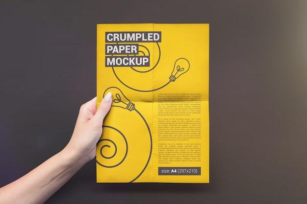 Vertikales gefaltetes modell des papiers in der hand Premium PSD