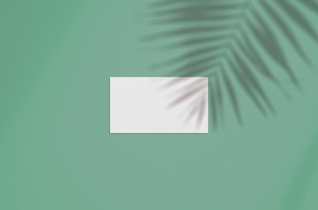 Visitenkarte mockup. natürliche überlagerungsbeleuchtung beschattet die palmblätter Premium PSD