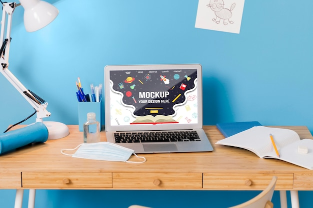 Vorderansicht der schulbank mit laptop und lampe Kostenlosen PSD