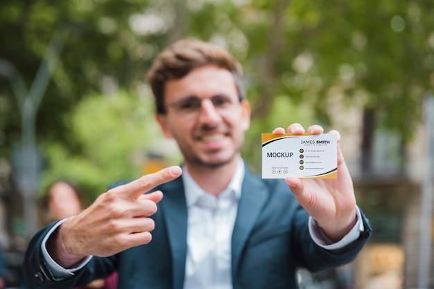 Vorderansicht des defokussierten geschäftsmannes, der auf eine visitenkarte zeigt und hält Premium PSD