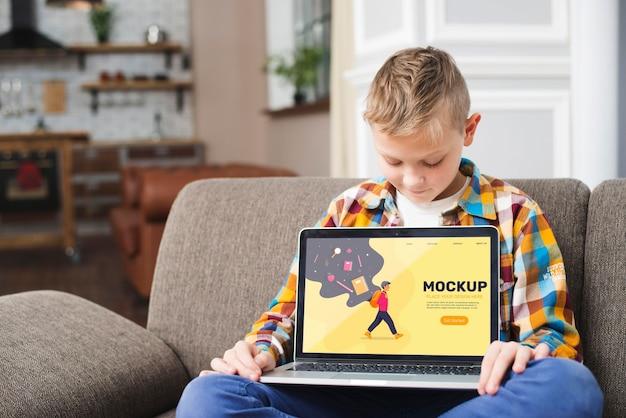 Vorderansicht des kindes auf der couch, die laptop hält Kostenlosen PSD