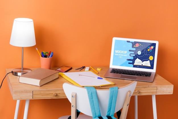 Vorderansicht des schreibtisches mit schulbedarf und laptop Kostenlosen PSD