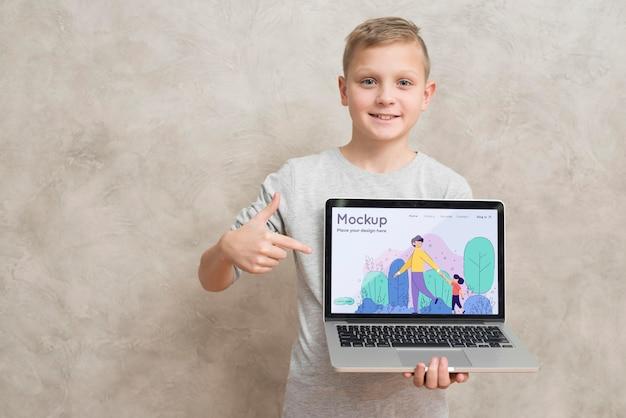 Vorderansicht des smiley-kindes, das laptop hält und zeigt Premium PSD