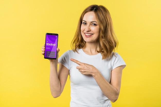 Vorderansicht frau, die ein mobiltelefon hält Premium PSD