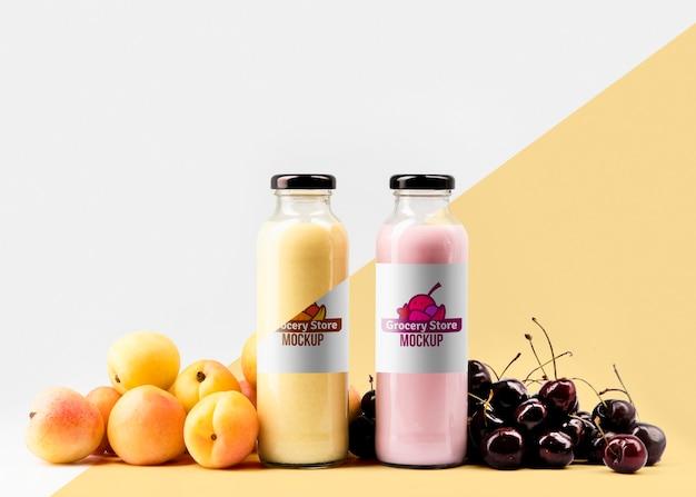 Vorderansicht von klaren saftflaschen mit kirschen und pfirsichen Kostenlosen PSD