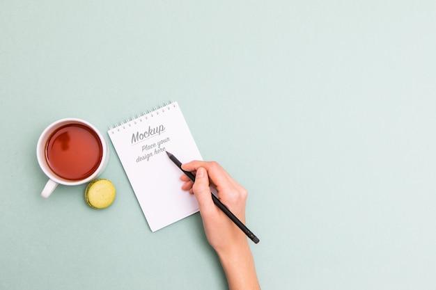 Weibliche hand, die schwarzen bleistift hält und in notizbuchmodell schreibt Premium PSD