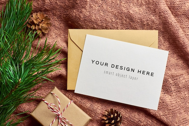 Weihnachtsgrußkartenmodell mit geschenkbox und kiefernzweig Premium PSD