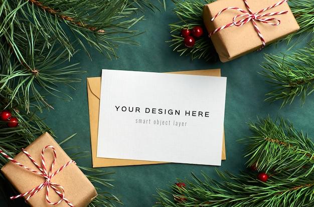Weihnachtsgrußkartenmodell mit geschenkboxen und kiefernzweigen Premium PSD