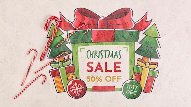 Weihnachtsverkauf mit einer eingewickelten geschenkbox und süßigkeiten Kostenlosen PSD