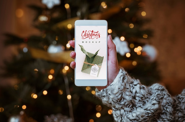 Weihnachtsverkaufsmodell mit der hand, die smartphone hält Kostenlosen PSD