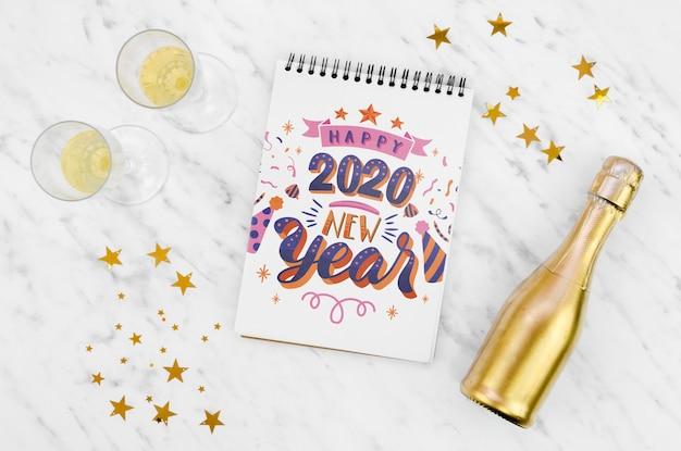 Weißer notizblock mit guten rutsch ins neue jahr-zitat 2020 und goldener flasche champagner Kostenlosen PSD