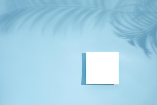 Weißes leeres leeres kartenmodell mit blumenschatten Premium PSD