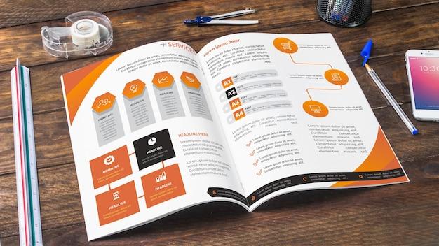 Zeitschriften- und smartphonemodell auf holztisch mit stiften und machthabern Kostenlosen PSD