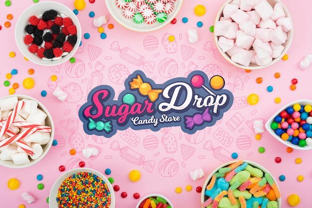 Zuckertropfen, umgeben von verschiedenen süßigkeiten Kostenlosen PSD