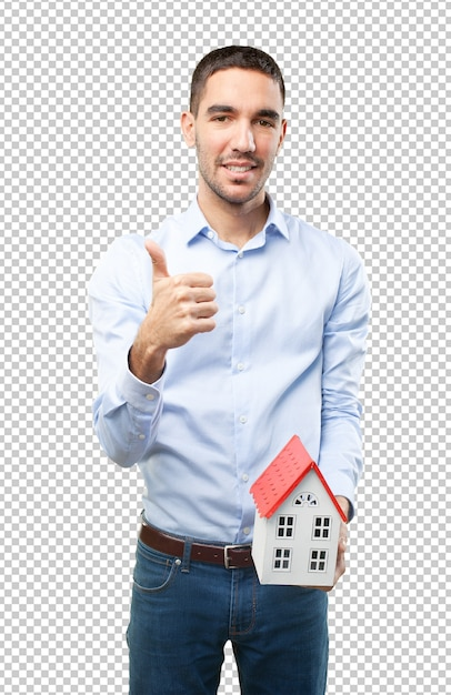 Zufriedener junger mann, der ein kleines haus hält Premium PSD
