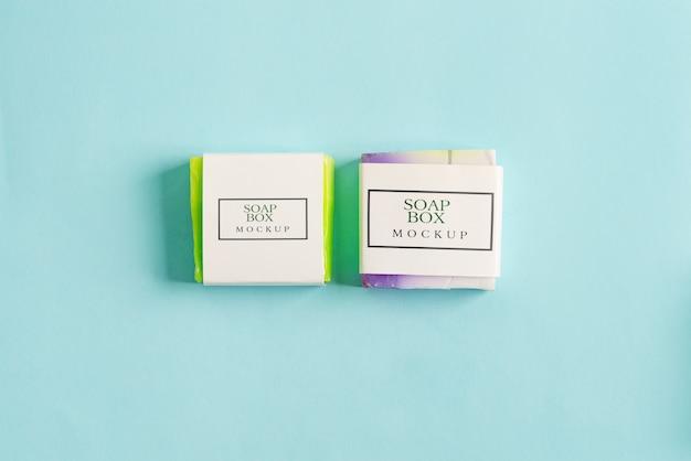 Zwei handgemachte seifenverpackungsbox-modellpaket mit bunter stückseife lokalisiert auf blauem hintergrund Premium PSD