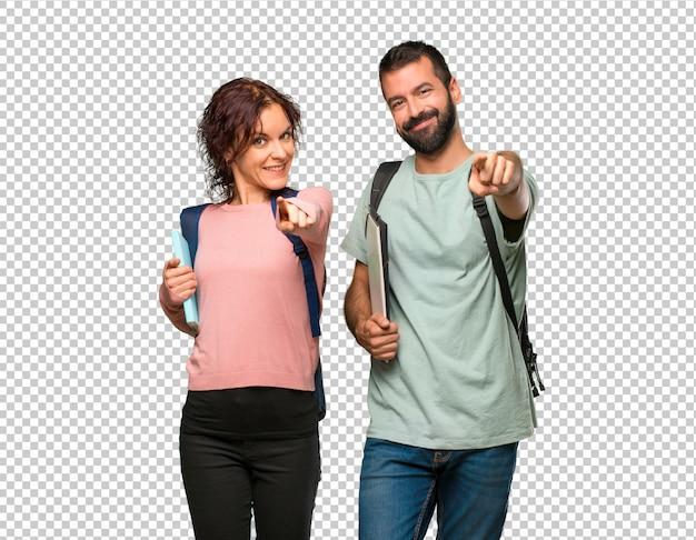 Zwei schüler mit rucksäcken und büchern zeigen mit einem selbstbewussten ausdruck auf sie Premium PSD