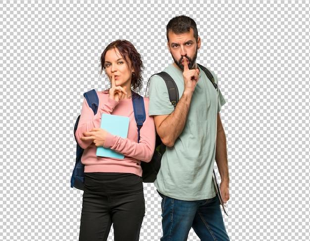 Zwei studenten mit rucksäcken und büchern, die ein zeichen des schließens des mundes und der ruhe zeigen, gestikulieren Premium PSD