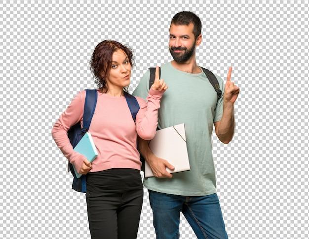 Zwei studenten mit rucksäcken und büchern, die einen finger im zeichen des besten zeigen und anheben Premium PSD