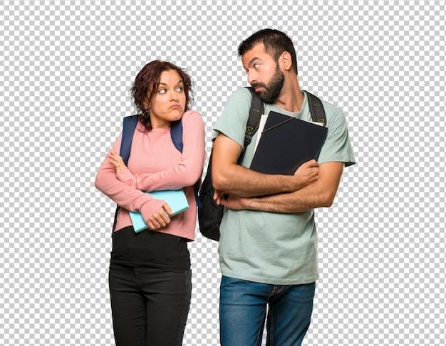 Zwei studenten mit rucksäcken und büchern, die unwichtige geste beim anheben der schultern machen Premium PSD