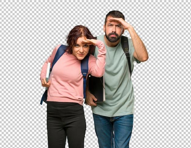 Zwei studenten mit rucksäcken und büchern, die weit weg mit der hand schauen, um etwas zu schauen Premium PSD