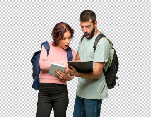 Zwei studenten mit rucksäcken und büchern ein buch lesend Premium PSD