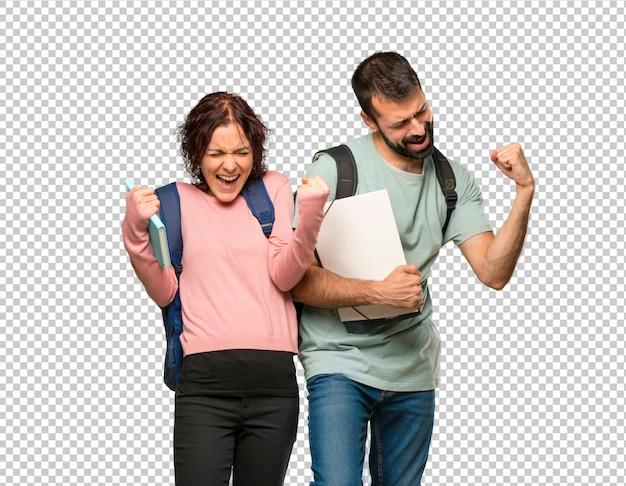 Zwei studenten mit rucksäcken und büchern feiern einen sieg und sind froh, einen preis gewonnen zu haben Premium PSD