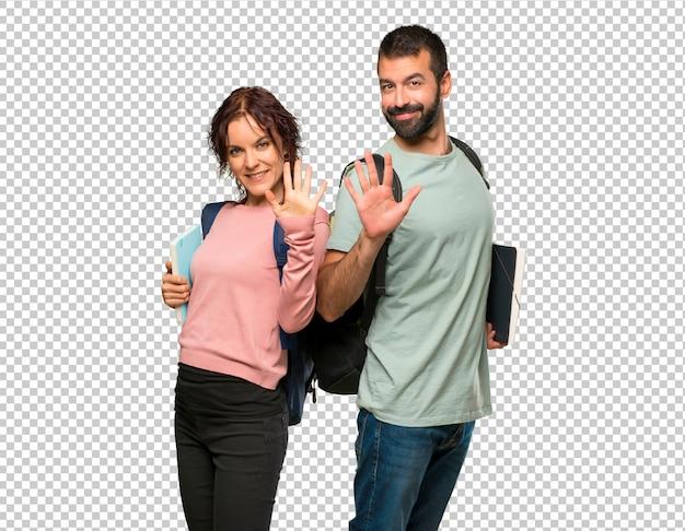 Zwei studenten mit rucksäcken und büchern zählen fünf mit den fingern Premium PSD