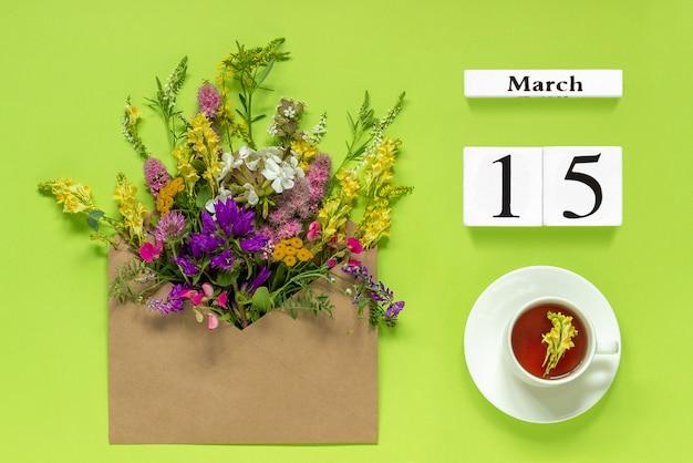 15 mars. tasse de thé, enveloppe kraft avec fleurs multicolores sur vert Photo Premium