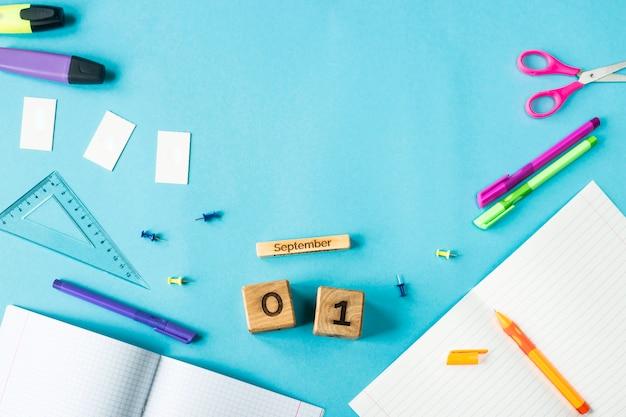 1er septembre sur un calendrier en bois parmi les fournitures pour étudier sur fond bleu Photo Premium