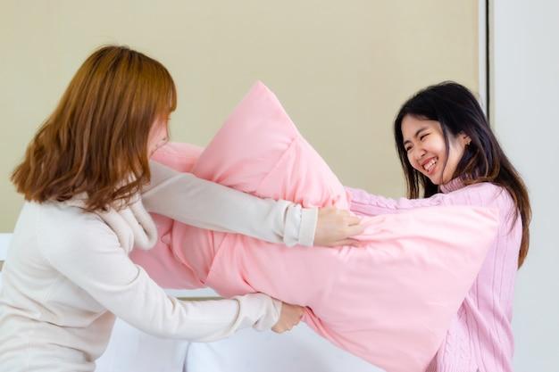 2 jeunes femmes jouent à des oreillers de combat Photo gratuit