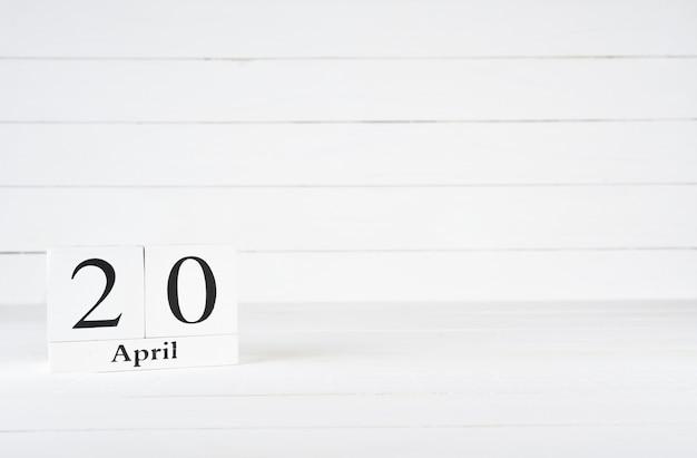 20 avril, jour 20 du mois, anniversaire, anniversaire, calendrier de bloc en bois sur un fond en bois blanc avec espace de copie du texte. Photo Premium