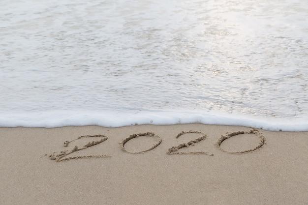 2020 écrit dans le sable sur la plage avant le nouvel an Photo Premium