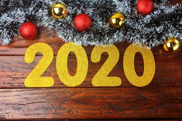 2020, nouvel an, chiffres dorés sur une table en bois rustique ornée Photo Premium
