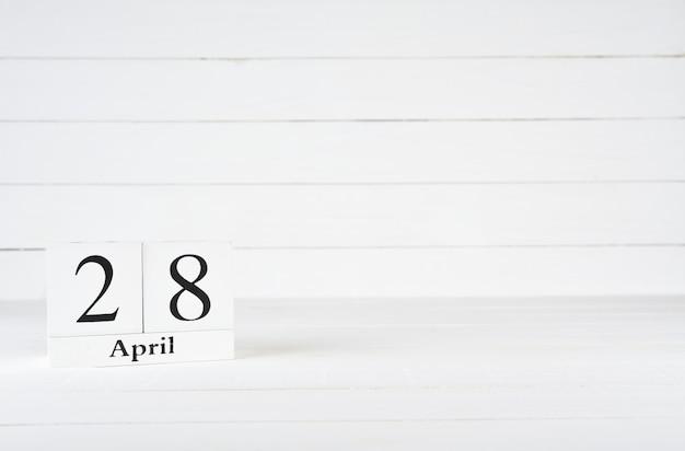 28 avril, jour 28 du mois, anniversaire, anniversaire, calendrier de bloc en bois sur un fond en bois blanc avec espace de copie du texte. Photo Premium