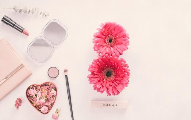 8 mars inscription de fleurs de gerbera avec cosmétiques sur table Photo gratuit
