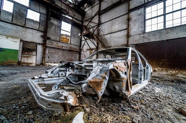 Abandonné dans le bâtiment vide l'ancien taxi rouillé de la voiture de tourisme. Photo Premium