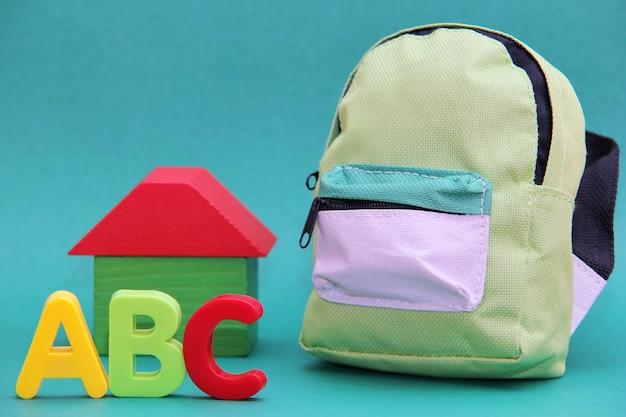 Abc - Lettres De L'alphabet Anglais à La Volonté D'une Maison En Bois Et D'un Sac D'école Sur Fond Vert. Photo Premium